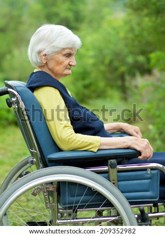 Handicapped sad elderly woman sitting in a wheelchair - stock photo
