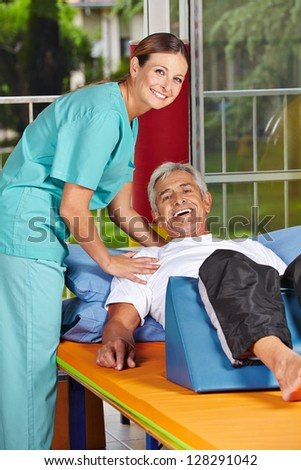 Handicapped senior man at rehab with physiotherapist - stock photo