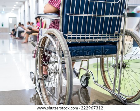 Handicapped senior woman patient on wheelchair in hospital - stock photo