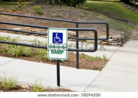 Handicapped sign at entrance of concrete ramp with black metal rail - stock photo