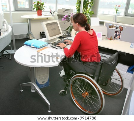 handicapped woman in wheelchair in a office working on a computer - stock photo