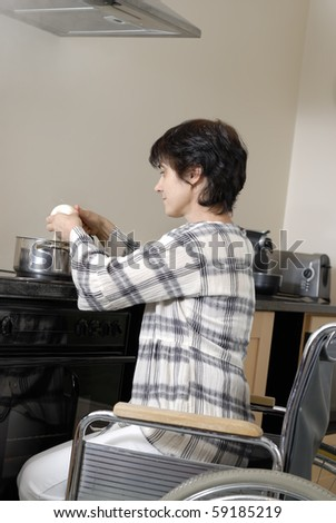 Handicapped woman in wheelchair preparing food - stock photo