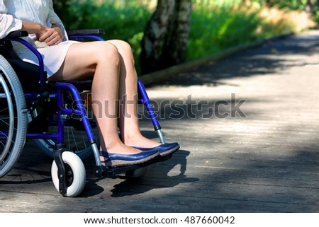 handicapped woman on a blue wheelchair in the park