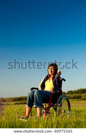 Handicapped woman on a wheelchair over a green meadow looking away - stock photo