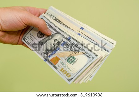 Handing a 100 dollar bill to viewer isolated on green background