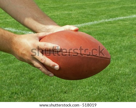 handing off the football - stock photo