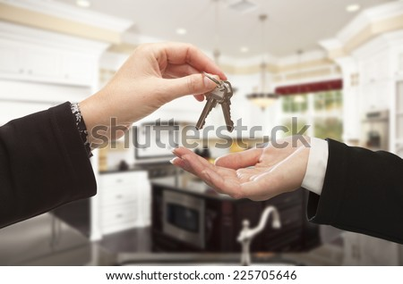 Handing Over New House Keys Inside Beautiful Custom Built Home. - stock photo