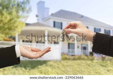 Handing Over The New House Keys with Home in the Background. - stock photo