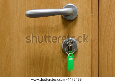 Handle and the lock with a key in a wooden door - stock photo