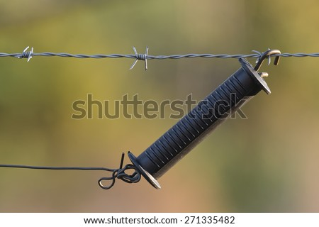 Handle for a electric fence that protects a green grass pasture - stock photo
