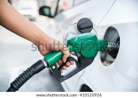 Handle fuel nozzle to refuel. Vehicle fueling facility. - stock photo