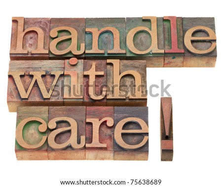 handle with care warning in vintage wood letterpress printing blocks, isolated on white - stock photo