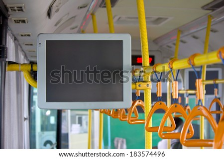 Handles and monitor for standing passenger inside a bus - stock photo
