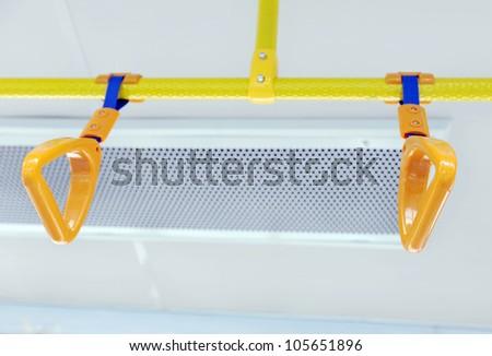 Handles for standing passenger inside a bus. - stock photo