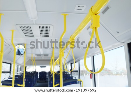 Handles for standing passenger inside a bus - stock photo