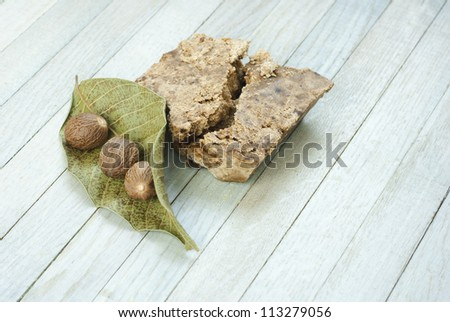 handmade african black soap and ingredients, shea butter nuts, dried leaves - stock photo