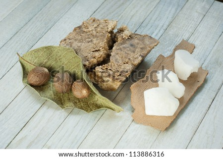handmade african black soap and ingredients, shea butter nuts, leaf and white shea butter - stock photo