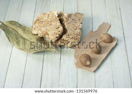handmade african black soap and ingredients, shea butter nuts, leaves - stock photo