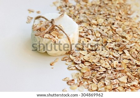 handmade bar of oatmeal soap organic healthy skin care white beige tones flakes scrub natural shallow DOF - stock photo