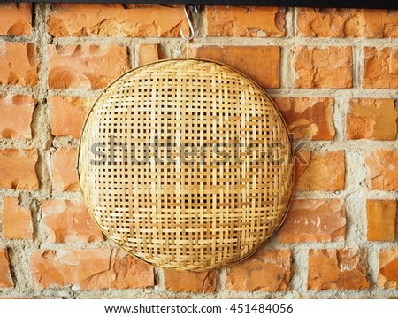 Handmade Basket witch weaving bamboo layer hanging on the red brick wall. - stock photo