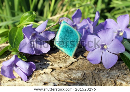 Handmade blue clay ring with wood violet in spring on the nature background - stock photo
