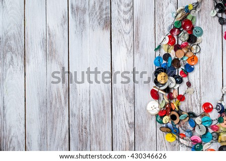 Handmade bright colored jewelry made of plastic buttons on white wooden background. Place for text. - stock photo