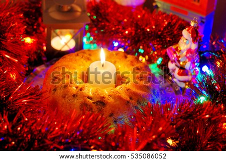Handmade cake, Christmas decor, candles, Santa Claus toy.
