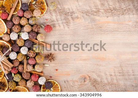Handmade chocolate candies collection, dried oranges, cinnamon, cloves, cardamom on wooden background. Free space for your text.