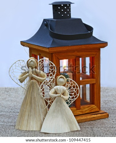Handmade christmas decoration angels  from straw and lantern with a  candle. Products of mass production.