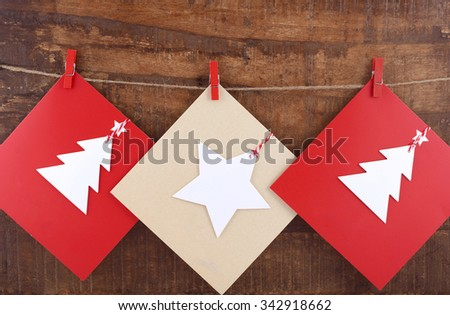 Handmade Christmas greeting card using cutout shapes on natural kraft paper hanging from pegs on string line.  - stock photo