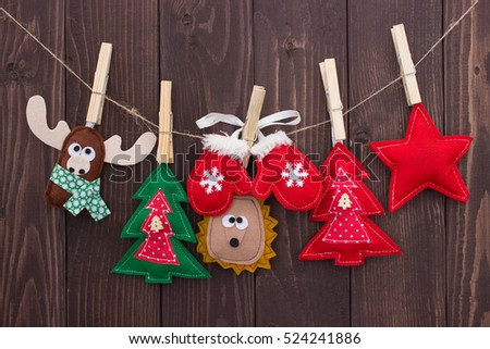 handmade christmas toys hanging on clothespin on wooden background