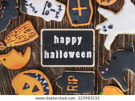 handmade cookies for Halloween and a blackboard with a greeting - stock photo