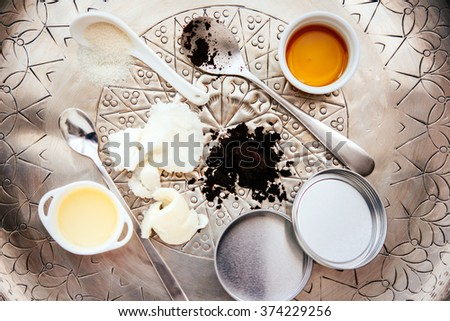 Handmade cosmetic ingredients - coconut and shea tree butter, olive oil, round coffee and sugar. Organic scrub and body cream. - stock photo