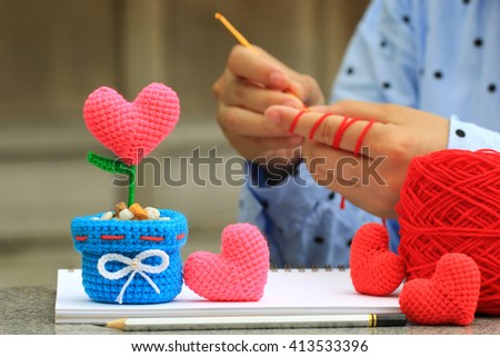 Handmade crochet heart and Woman with her crochet, Valentine's Day - stock photo