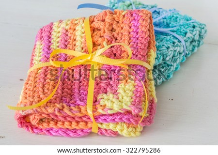 Handmade crocheted dishcloths made with different stitches and multicolored yarn. - stock photo