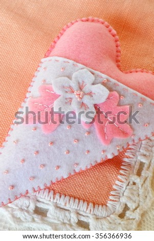 Handmade felt heart - symbol of Valentines Day, on coral background  - stock photo