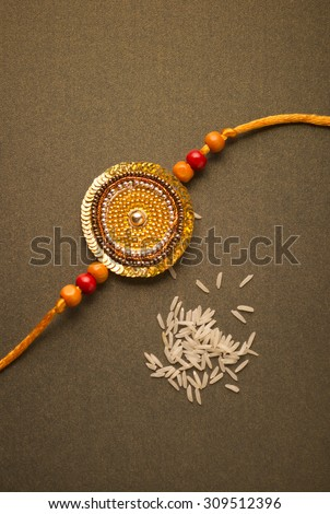 Handmade golden Rakhi with scattered white rice grains. - stock photo