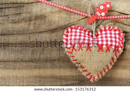 Handmade heart clipped to a Christmas ribbon with a Christmas tree shaped clothespin against rustic wooden background. with copy space - stock photo