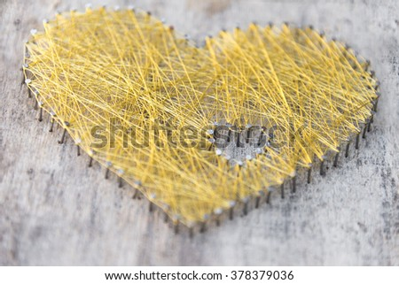 Handmade heart made of nails on wooden board with wowen gold string - stock photo