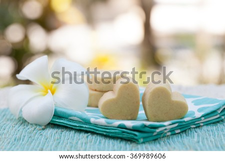 Handmade heart shape cookies on wooden plate and blue napkin Outdoor background Frangipani flower  - stock photo