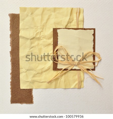 Handmade invitation card or album book cover decorated with wrinkled paper broken edges frame border and bow. - stock photo