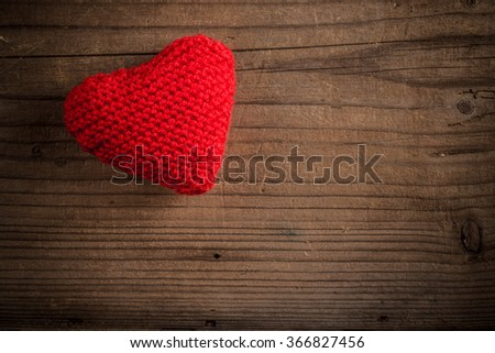 Handmade knitted heart on wooden background