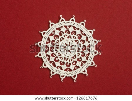 Handmade lace doily, an example of the famous paska cipka needle lace from Pag Island, Croatia, against red background - stock photo