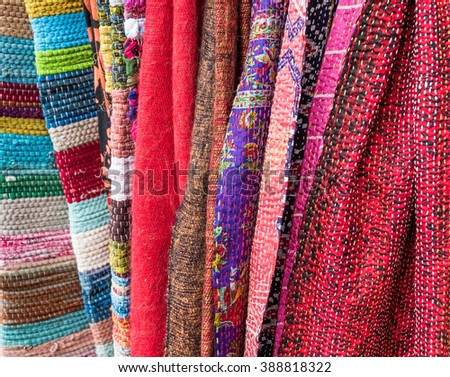 Handmade multicoloured fabric hanging in a market stall.