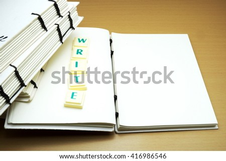 Handmade notebooks on wooden background. Scrabble letters spelling WRITE concept. - stock photo