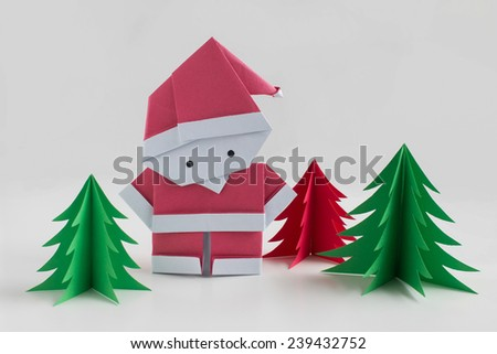 Handmade origami paper craft Santa Claus with red and green christmas trees on white background - stock photo