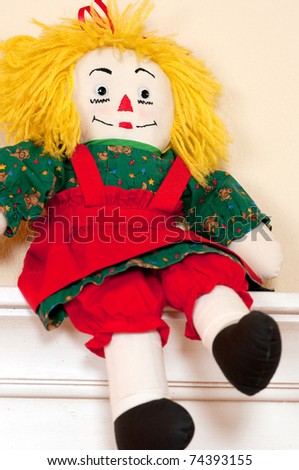 Handmade ragdoll with yellow hair wearing red and green dress sitting on white tone shelf against beige background, portrait orientation - stock photo