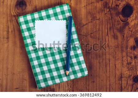 Handmade recipe cookbook on kitchen desk with blank label as copy space, top view - stock photo