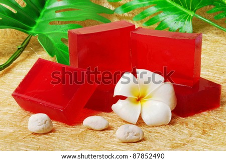 Handmade soap bars on Luffa mat with Frangipani flowers and leaf. - stock photo