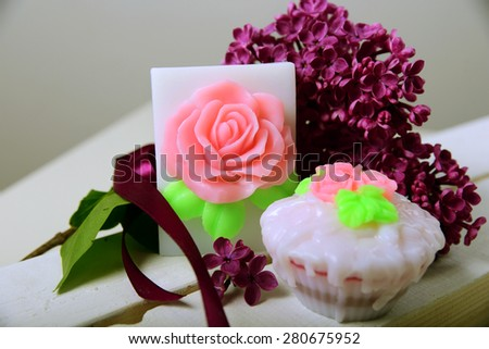 Handmade soap. Shaped cake and roses. The branch of lilac with a satin ribbon - stock photo